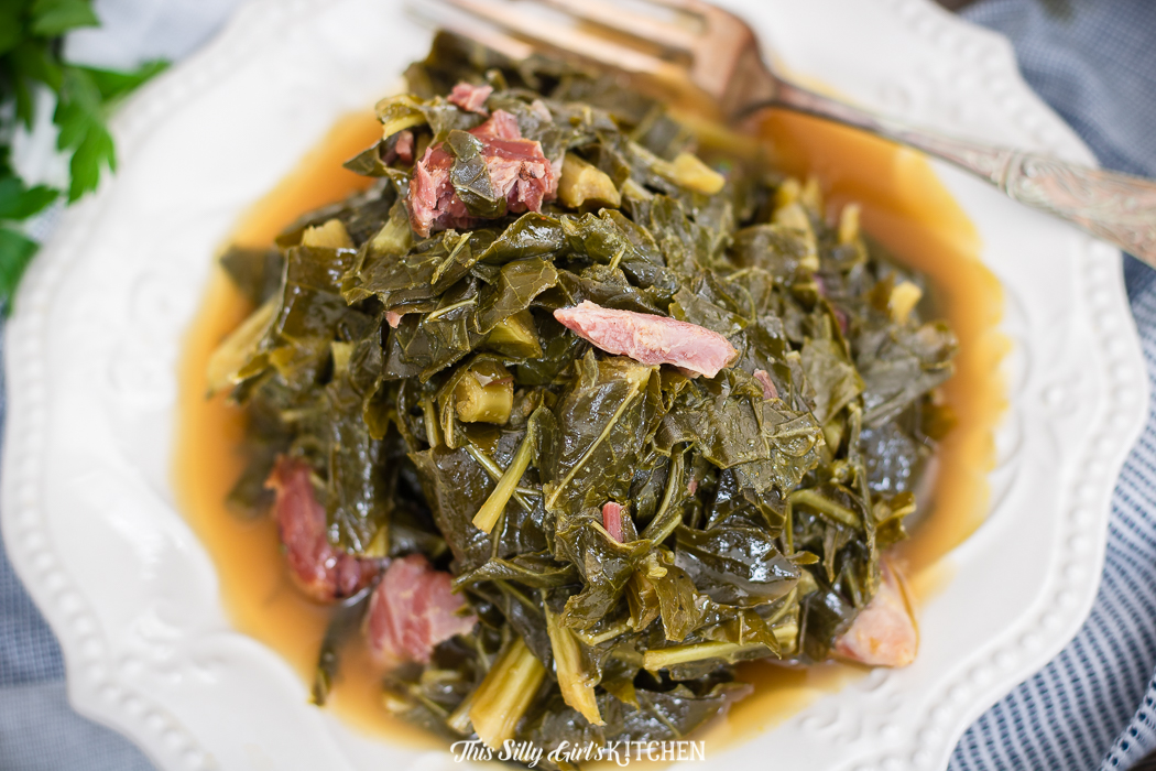 Close up of collards on plate with fork showing ham pieces