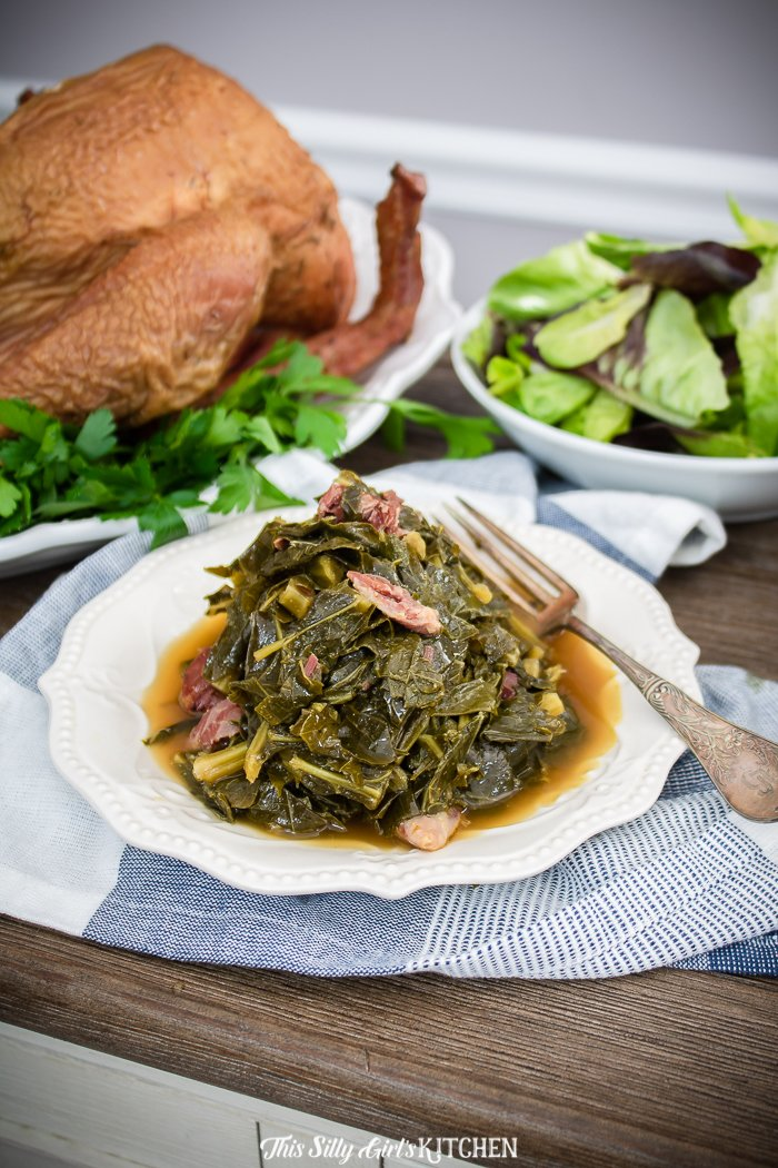 Table with turnkey, salad and plate full of collard greens