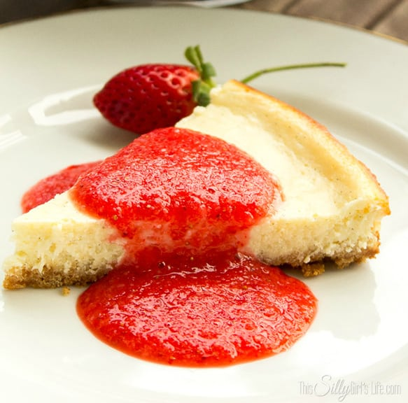 Vanilla Bean Cheesecake with Fresh Strawberry Sauce, It's nice a creamy and not overly sweet vanilla cheesecake. The tartness from the strawberry sauce really sets it off!