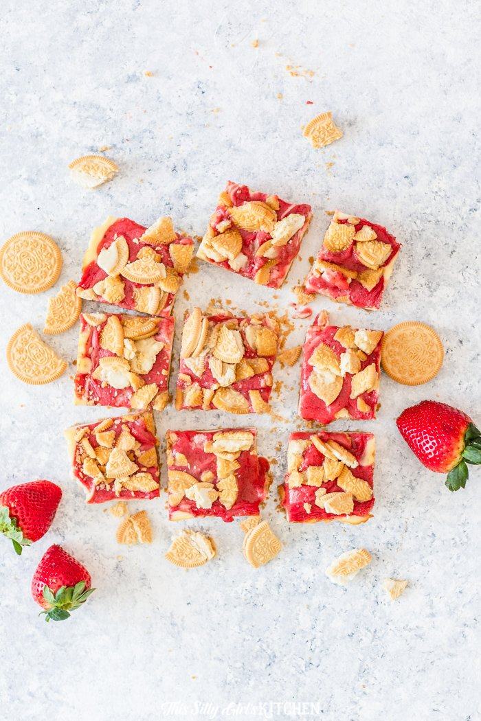 Strawberry Cheesecake Bars, golden Oreo crust with a creamy cheesecake filling, and strawberry sauce. #recipe from thissillygirlskitchen.com #cheesecake #cheesecakebars #strawberrycheesecakebars #goldenoreostrawberrycheesecakebars