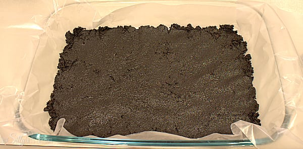 Taking that Oreos, place into a food processor and turn into crumbs, you may have to do this in batches. Take half of the crumb and mix with the melted butter. Line a 13x9 inch pan with parchment or wax paper and press the crumbs into the bottom of the pan to form a crust. Set aside.