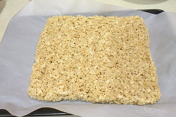Melt butter in a large sauce pot over medium low heat. Add in marshmallows and let melt, stirring constantly. As soon as all the marshmallows have melted, take off the heat and add in the rice cereal. Mix and mix until all the cereal is coated. Spread mix over a sheet tray lined with parchment paper, for easy spreading spray a spatula with cooking spray or your fingers. Form into the shape you wish (try to get a flat surface), set aside, covered with plastic wrap for at least one hour to set.