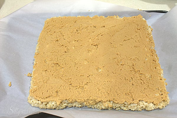 Cream together the butter and peanut butter with a hand mixer over medium speed. Add in the powdered sugar until combined. Add in the milk and vanilla. Whip on medium speed until light and fluffy about 3 minutes. Spread over rice krispies treats in a thin even layer.
