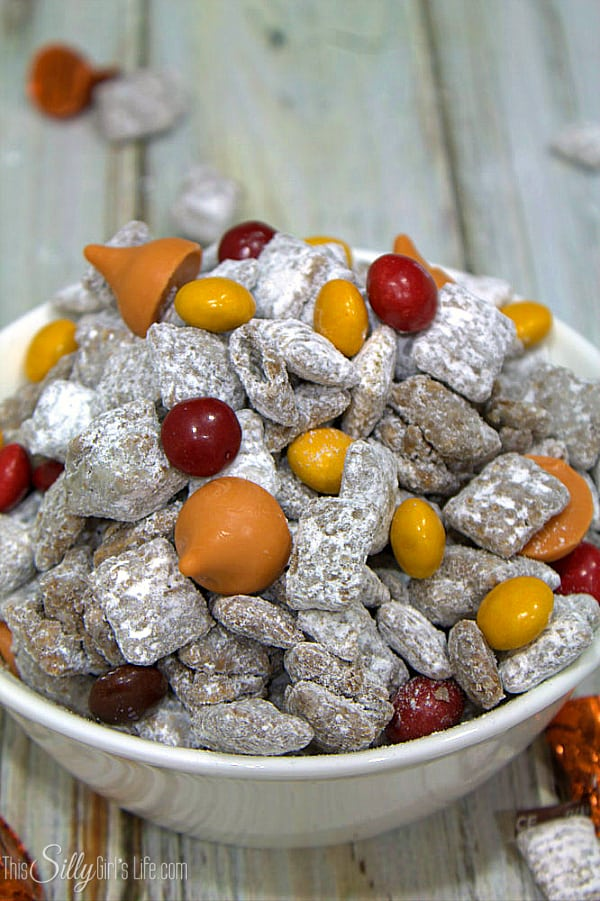 Pumpkin Patch Munch, traditional muddy buddies dusted with pumpkin pie spice powdered sugar and loaded with peanut butter m&m's and pumpkin spice kisses! - http://ThisSillyGirlsLife.com