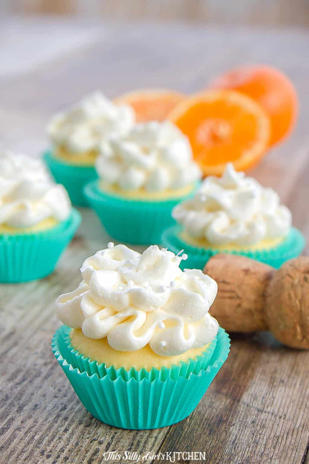 Mini Mimosa Cupcakes, bite-sized cupcakes infused with fresh squeezed orange juice and topped with fluffy champagne buttercream frosting! #recipe from thissillygirlskitchen.com #cupcakes #minicupcakes #mimosa #mimosacupcakes #orange #champange #buttercream