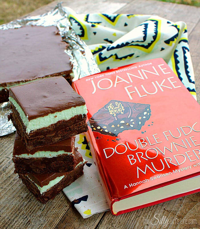 Stacked brownies next to Double Fudge Brownie Murder Book