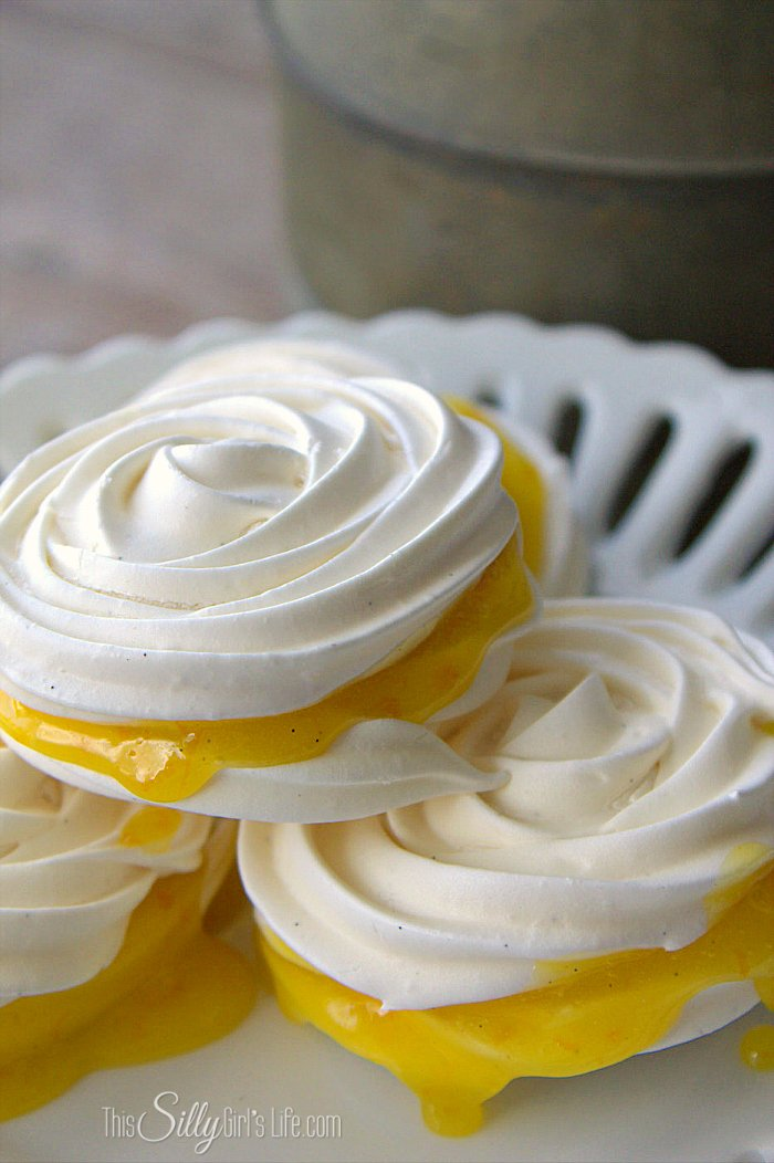 Orange Curd Vanilla Meringue Cookies, homemade orange curd sandwiched between light, airy and crisp classic vanilla meringue rosettes. - ThisSillyGirlsLife.com