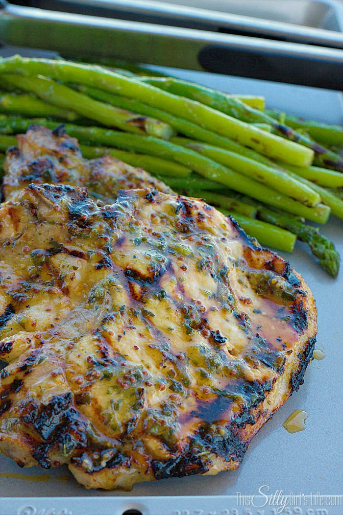Herb Marinated Grilled Pork Chops, a moist and delicious marinade for pork (and chicken!) consisting of herbs, honey and whole grain mustard. - ThisSillyGirlsLife.com