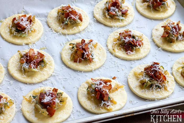 Caramelized Onion Bacon Tarts, sweet onions, salty bacon, herbs and Parmesan cheese atop puffed pastry make this an easy and elegant appetizer! from ThisSillyGirlsLife.com #caramelizedonion #bacon