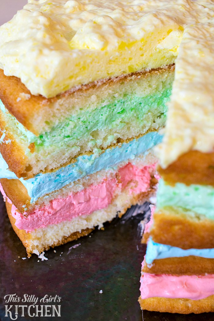Rainbow Jello Cloud Cake, white cake layered between different flavors of light and airy Jello frosting! from ThisSillyGirlsLife.com #jellofrosting