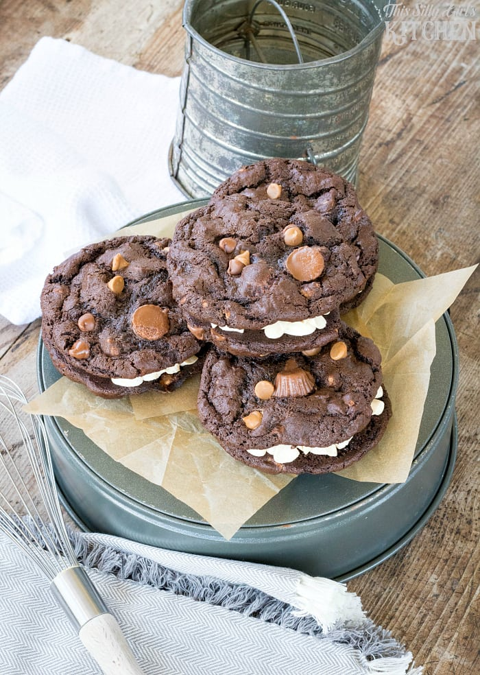 Chocolate Peanut Butter Overload Sandwich Cookies, soft chocolate cookies with peanut butter frosting and peanut butter cups! from ThisSillyGirlsLife.com