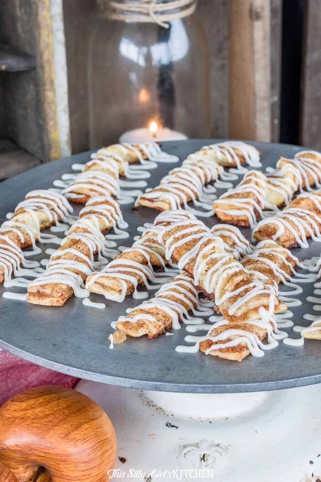 Apple Cinnamon Twists, apple pie turned into a breakfast treat, dripping with vanilla bean glaze! #recipe from ThisSillyGirlsKitchen.com #apple #cinnamon #cinnamontwists #applecinnamon #piecrust