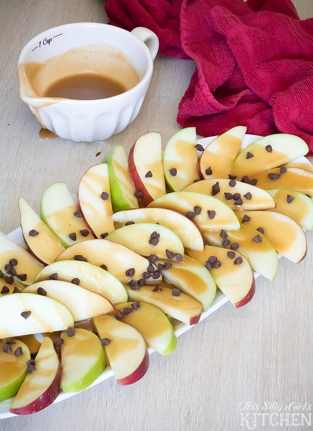 Peanut Butter Apple Nachos, a fun fall snack! Peanut butter sauce is drizzled over apple slices and garnished with mini chocolate chips. from ThisSillyGirlsKitchen.com #ad