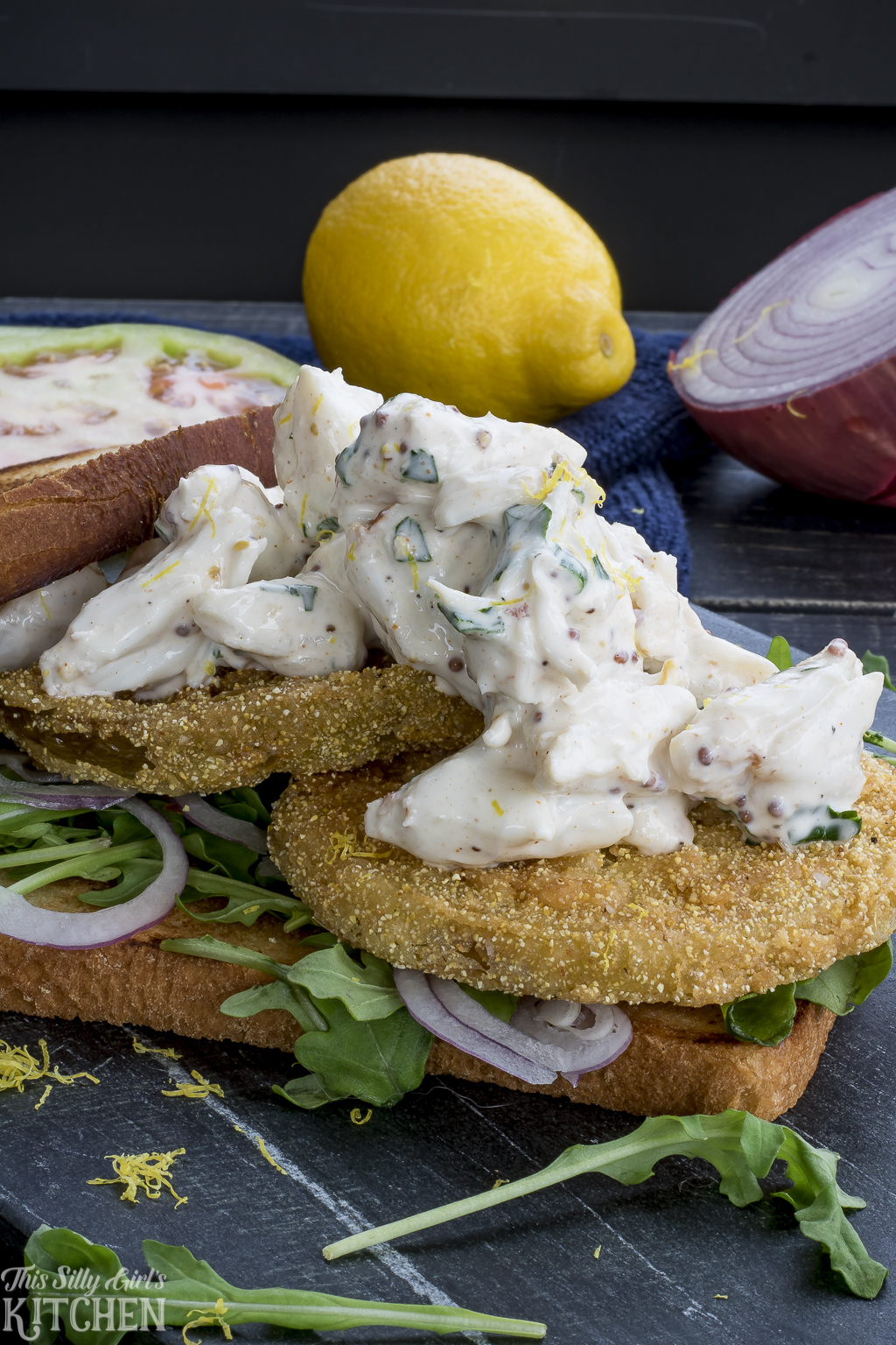 Fried Green Tomato Crab Salad Sandwiches, jumbo lump crab salad over fried green tomatoes, arugula and red onion, all between two slices of bread! Recipe from ThisSillyGirlsKitchen.com