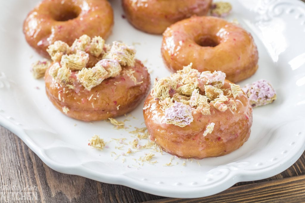 Strawberry Glazed Cereal Doughnuts, classic yeast doughnuts dipped in sinful strawberry glaze and garnished with a fun cereal topping! Recipe from ThisSillyGirlsKitchen.com