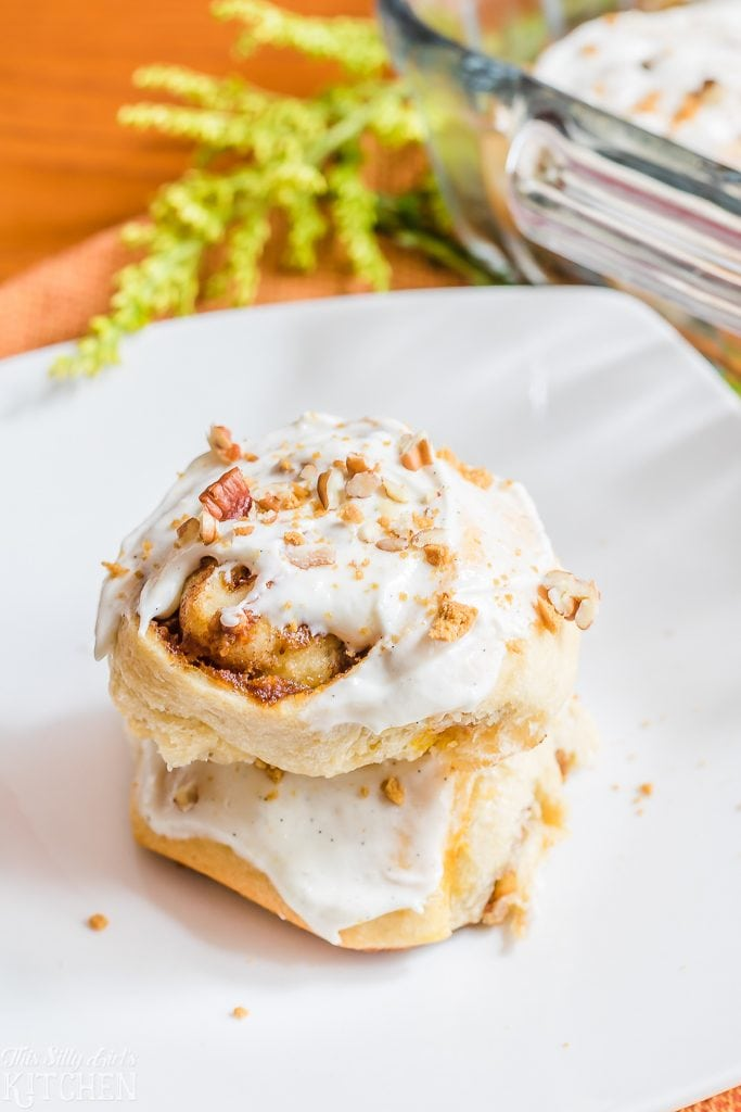 Pumpkin Cinnamon Rolls in just 30 minutes with crunchy pecans and a sweet marshmallow glaze!  Recipe from ThisSillyGirlsKitchen.com
