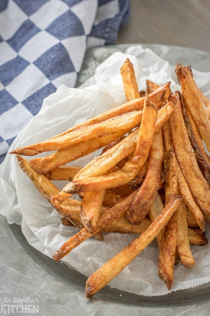 Homemade French Fries, your favorite restaurant staple at home! #Recipe from ThisSillyGirlsKitchen.com #frenchfries #homemadefrenchfries #homemadefries #stovetopfries #ovenfries