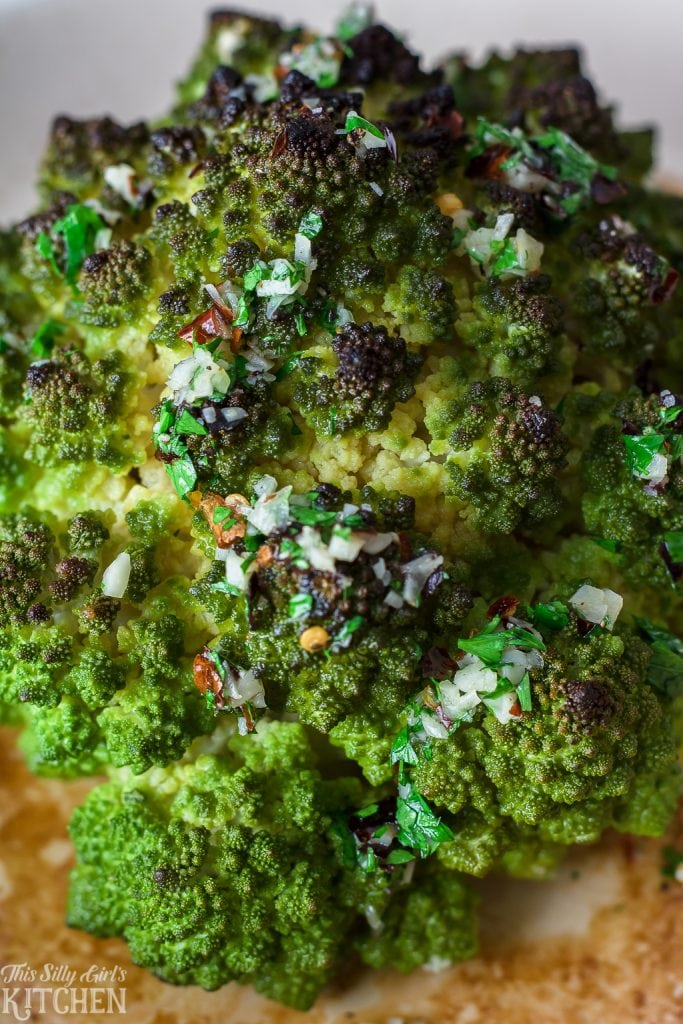 Whole Roasted Romanesco Cauliflower, ready in 30 minutes and drizzled with an addictive garlic butter sauce! Recipe from ThisSillyGirlsKitchen.com