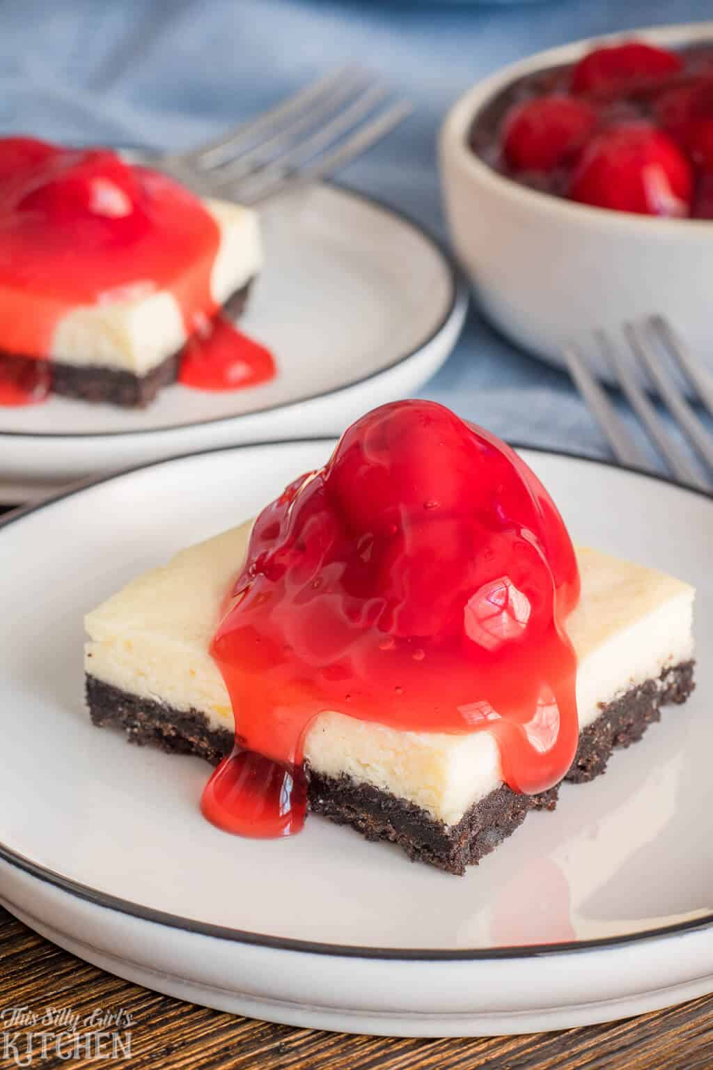 Easy Cherry #Cheesecake Bars, silky cheesecake on an addictive #Oreo crust, topped with cherries! #Recipe from ThisSillyGirlsKitchen.com #cherrycheesecake #cheesecakebars #dessert