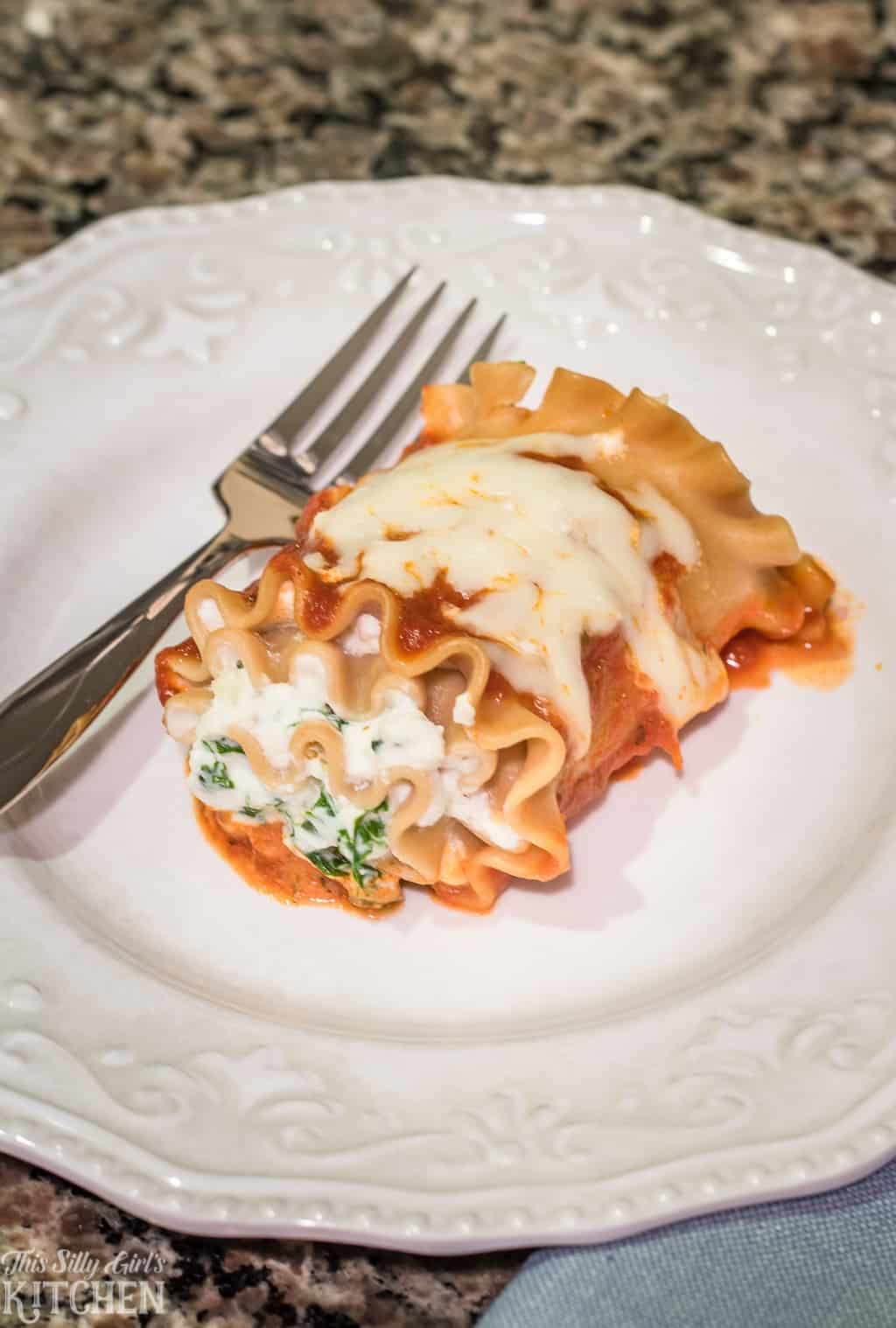 Skinny Lasagna Rolls, little packages filled with ricotta cheese and sauteed kale, a lightened up recipe full of flavor! #Recipe from ThisSillyGirlsKitchen.com #lasagna #skinny #lasagnarolls