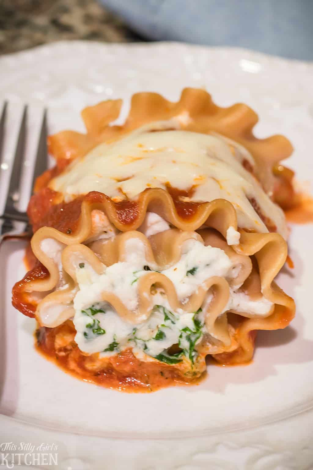 Lasagna Roll-Ups, little packages filled with ricotta cheese and sauteed kale, a lightened up recipe full of flavor! #Recipe from ThisSillyGirlsKitchen.com #lasagna #skinny #lasagnarolls