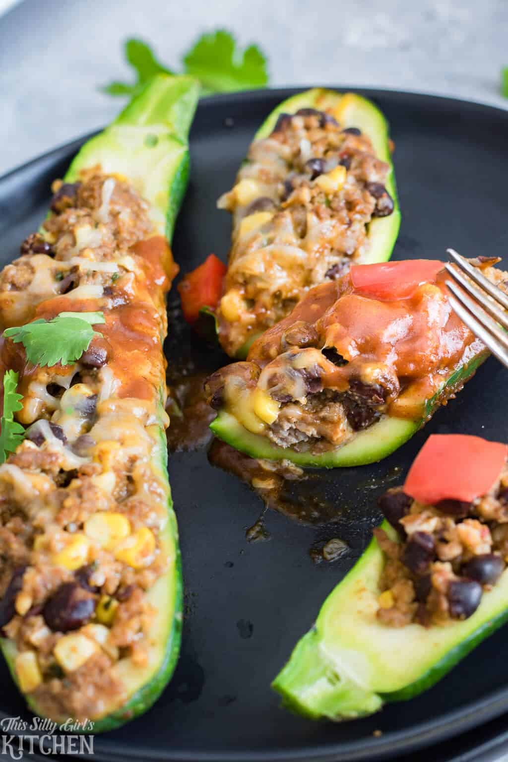 Enchilada Stuffed Zucchini, a satisfying, easy dinner the whole family will love! #Recipe from ThisSillyGirlsKitchen.com #Enchilada #StuffedZucchini