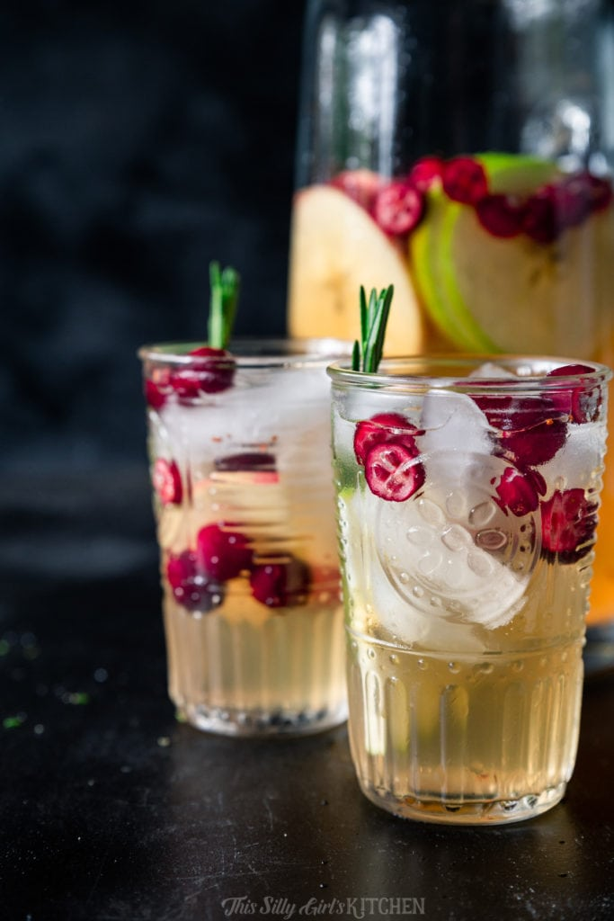 This white wine sangria is light, refreshing and effervescent, with flavors of vanilla, apples, and cranberries. #recipe from thissillygirlskitchen.com #sangria #whitewinesangria #wintersangria #holidaysangria #cranberry #apple #cocktail