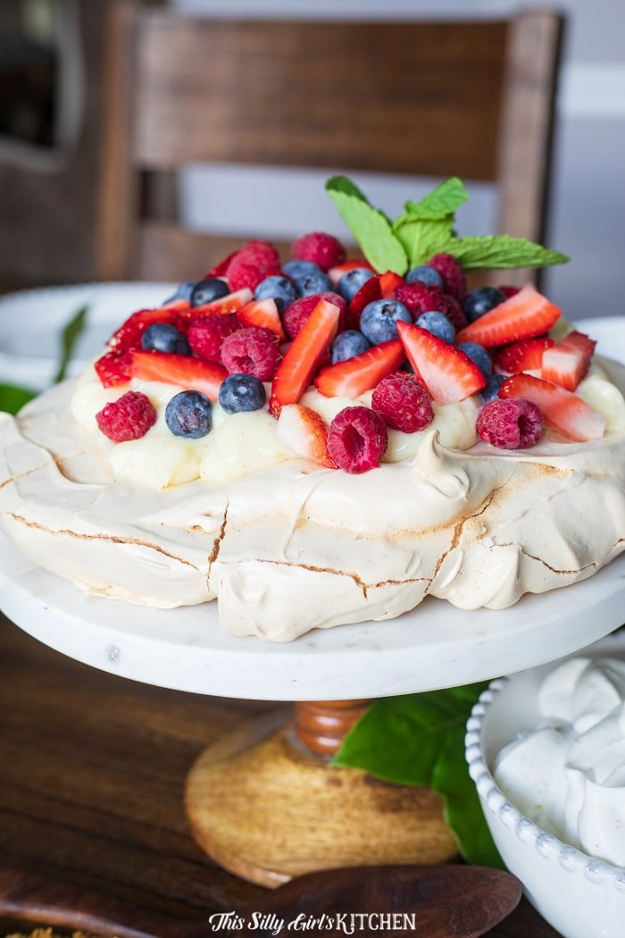 Berry Pavlova Recipe, this classic vanilla pavlova is topped with pastry cream and fresh berries. #recipe from thissillygirlskitchen.com #pavlova #berrypavlova #pavlovarecipe #berrypavlovarecipe