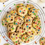 M&M Chocolate Chip Peanut Butter Cookies stacked on wire rack with cookies surrounding it