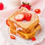 Square image of stacked French toast on white plate with strawberries