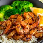 Close up square image of Blackened Shrimp over rice with vegetables