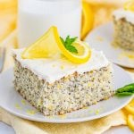 Square photo of slice of cake on white plate topped with lemon and mint