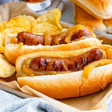 Square image of two brats in buns on tray with chips.