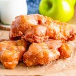 Square image of finished Apple Fritters stacked on top of one another.